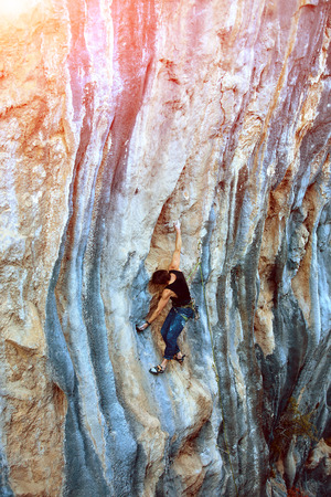 clambering: rock climber climbs on a rocky wall
