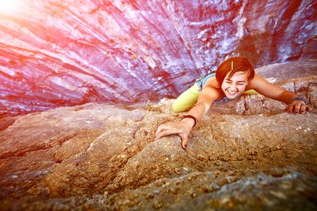 klimmer: vrouwelijke rock klimmer klimt op een rotsachtige muur, Houd een hand op de rots en lacht. gericht op de hand