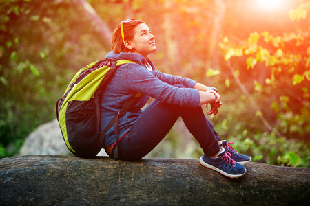 Active healthy woman hiking in beautiful forest. Portrait of happy smiling young woman resting of forest clearing during hike holidays. Stock Photo
