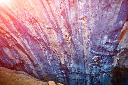 escalando: escalador sube en una pared rocosa