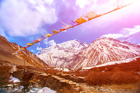 recline: Hotel in mountains and traditional flags with prayer on the foreground.   Trek around Annapurna mount. Tilicho lake region. Nepal