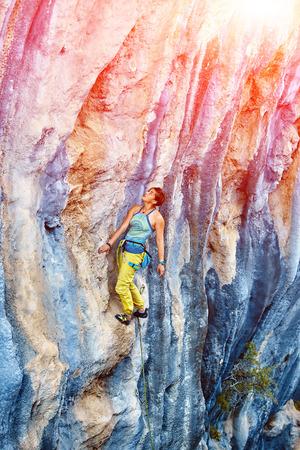 lead rope: female rock climber climbs on a rocky wall