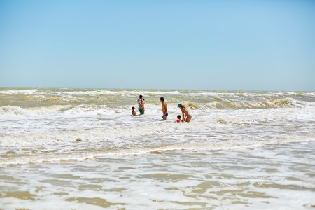 granola: familia en el mar con olas grandes