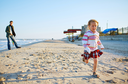 douther: girl running on the sea beach at the sunset Stock Photo