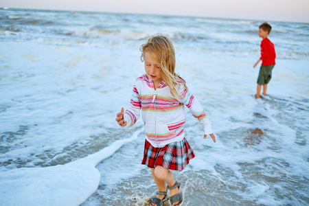 cute little girl playing with sand and vawes on the sunny beach