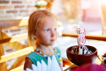 five years': Portrait of little pretty girl with birthday ice cream, five years Stock Photo
