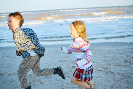 douther: kids running on the sea beach at the sunset Stock Photo