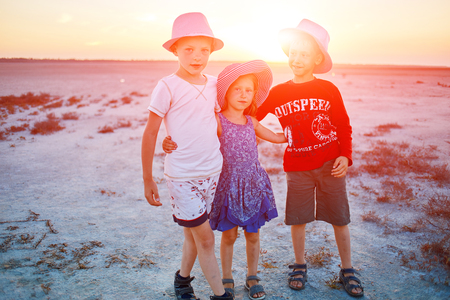 douther: kids in the desert at the  sunset, two boys and one girl