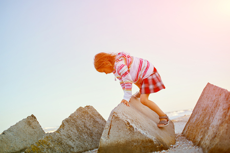 douther: girl playing on the sea beach at the sunset Stock Photo