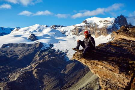 snow climbing: hiker at the top of a pass with backpack enjoy sunny day in Alps. Switzerland, Trek near Matterhorn mount.