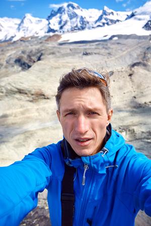 morning sun: hiker  at the top of a pass  making selfie against  snow capped mountains in Alps. Switzerland, Trek near Matterhorn mount.