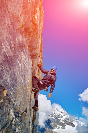 overhanging: Young man climbs on a rocky wall, against a blue sky Stock Photo