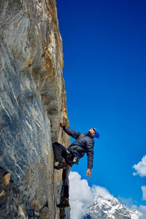 escalando: Hombre joven que sube en una pared rocosa, contra un cielo azul Foto de archivo