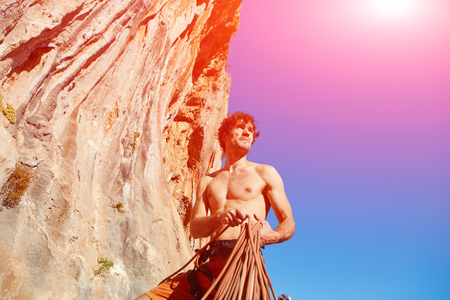 atraction: attractive muscular male climber with the rope under the cliff against blue sky