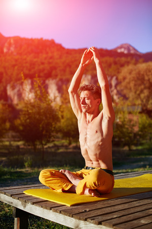 asanas: young man doing yoga in the early morning on the garden terrace of the house