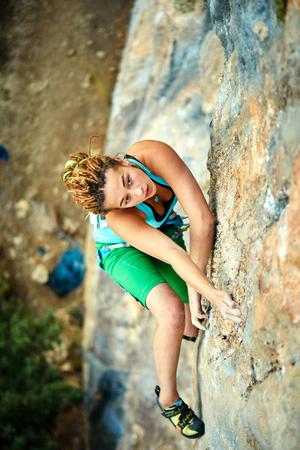 climbing: escalador de roca femenino se sube en una pared rocosa