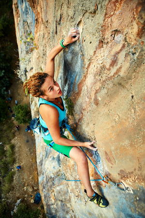 extremes: female rock climber climbs on a rocky wall