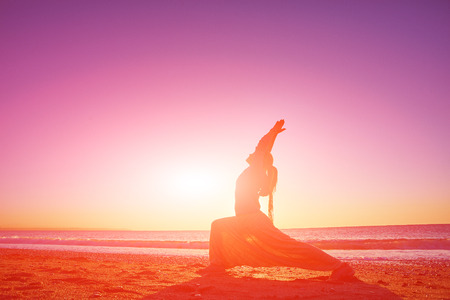 serene people: young woman doing yoga on the beach against sea and blue sky at early morning Stock Photo