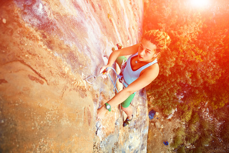 man climbing: female rock climber climbs on a rocky wall