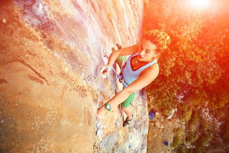 stijger: vrouwelijke rock klimmer klimt op een rotsachtige muur