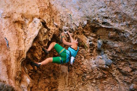 escalando: escalador de roca femenino se sube en una pared rocosa