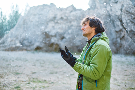 lead rope: man rock climber preparing to climb under the cliff at winter Stock Photo