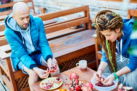 man and young woman with  dreadlocks in the garden on the veranda of the house eating pomegranates Stock Photo