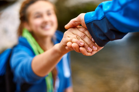 Helping hand - hiker woman getting help on hike smiling happy overcoming obstacle. Tourist backpackers walking in autumn forest. Young couple traveling. Stockfoto