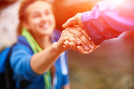 Mano amiga - caminante de la mujer Obtención de ayuda en alza sonriente feliz superación de obstáculos. mochileros turísticos caminando en el bosque de otoño. itinerante pareja joven.