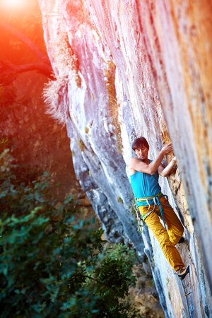 lead rope: male rock climber climbs on a rocky wall Stock Photo