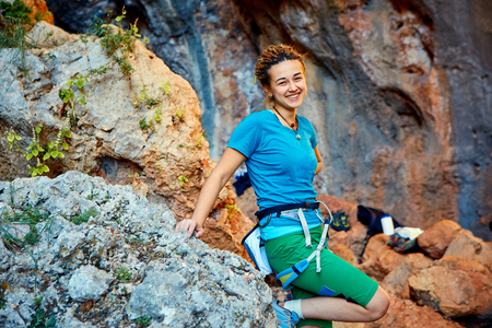 lead rope: female rock climber stands on a rocky wall background