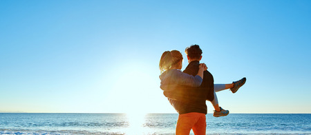 happy attractive man and woman walking on the sunny beach over the blue sky. man holding a woman on the hands.