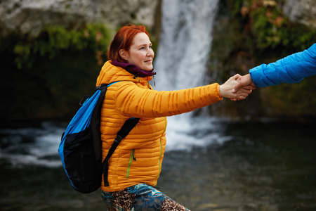 overcoming: Helping hand - hiker woman getting help on hike smiling happy overcoming obstacle. Tourist backpackers walking in autumn forest. Young couple traveling. Stock Photo