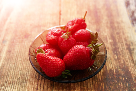 fresh strawberries on a plate on a wooden backgroung