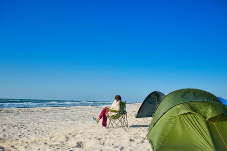 백그라운드에서 청록색 바다와 푸른 하늘과 외로운 해변에서 텐트와 야영