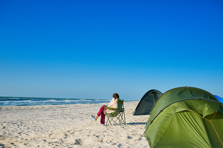 lonesome: camping with a tent at a lonesome beach with a turquoise sea and blue sky in the background Stock Photo