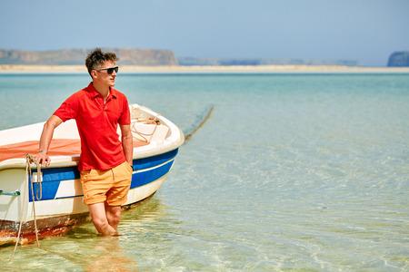 uomo in piedi nel mare vicino alla barca. uomo che indossa in camicia polo rossa e occhiali da sole