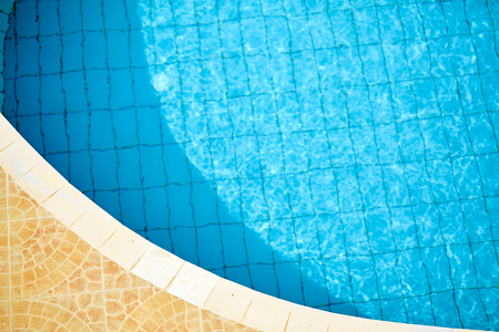 edge of the Swimming Pool. paving brick floor with blue shine water background