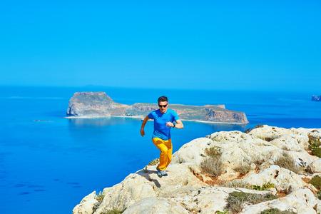 pursue: man runs on a rock against a  blue sea