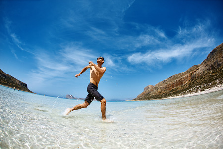 bared: strong athletic man  with bared torso running on the beach along the sea front