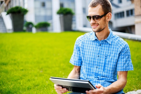 univercity: young man, wearing in blue t-shirt and sunglasses  with thin, elegant flexible laptop  on the green background in the park or business center or univercity area