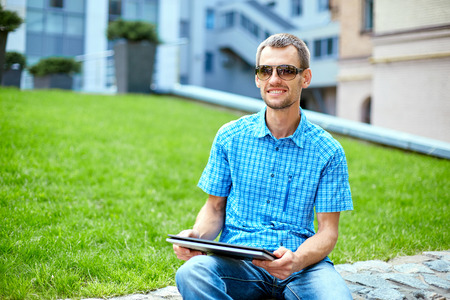 univercity: young man, wearing in blue t-shirt and sunglasses  with thin, elegant flexible laptop  on the green background in the park or business center or univercity area. learning or business concept Stock Photo