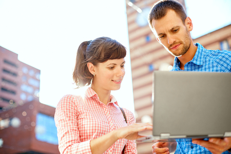univercity: young man, wearing in blue t-shirt and sunglasses and woman with thin, elegant flexible laptop  on the green background in the park or business center or univercity area. learning or business concept
