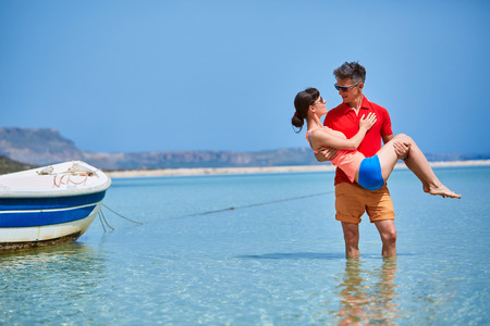 adult cruise: couple standing in the sea  near the boat.