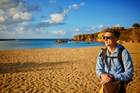 adult cruise: man standing at the sea on the beach wearing in blue shirt and sunglasses Stock Photo