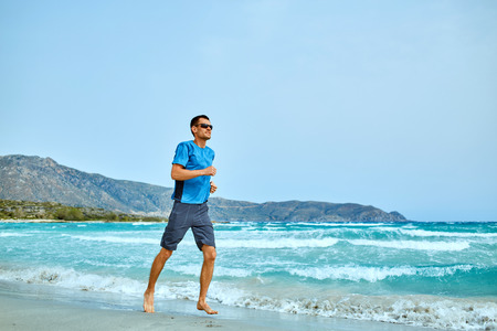strong athletic man running on the beach along the sea front Stock Photo