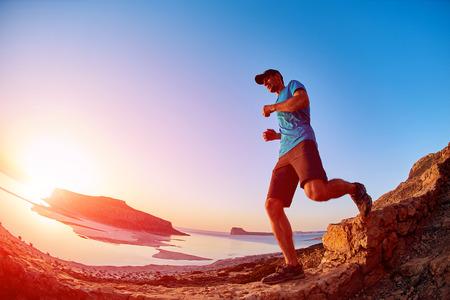 randonneur mâle, voyageur court sur la piste contre la mer et le ciel bleu au coucher du soleil. plage Balos sur fond, Crète, Grèce