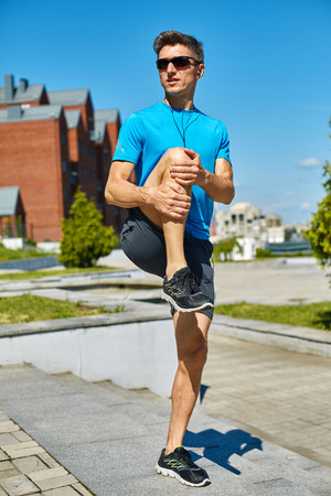man runner athlete warming up and stretched before jogging along a city bay at the early morning. man fitness sunset jogging workout wellness concept. Stock Photo