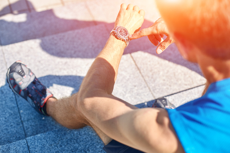 Man athlete doing running and watching the watch in park Stock Photo