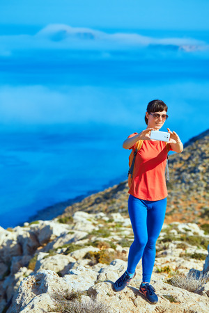female traveler with backpack standing on the cliff against sea and blue sky at early morning. Balos beach on background, Crete, Greece. Woman taking a photo in smartphone